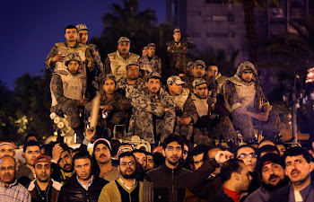 Anti-government protesters and Army soldiers watch and listen to the statement of Egyptian Presiden