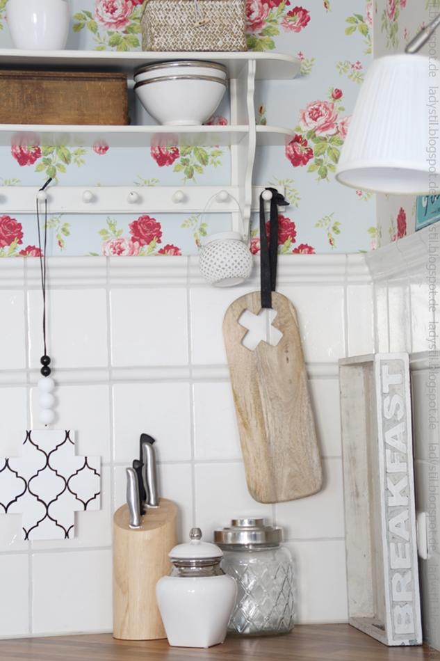 Blick in eine Küchenecke mit geblümter Tapete, Wandregal, und Holzfarbenen sowie weißen Utensilien und einer Cross-Chain