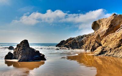 Hermosa playa con arenas blancas y rocas marrón