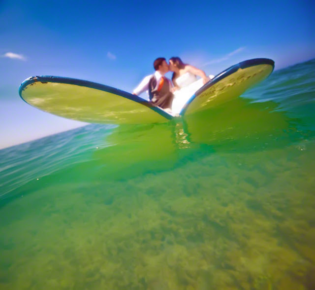 bride and groom surfing in their wedding dress, top hawaii wedding locations, best places for a destination wedding in hawaii