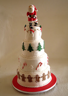 Big Christmas cake decorated with gingerbread mans,Xmas trees,Candy canes, snowmans around very different cake with Santa Claus walking on it picture