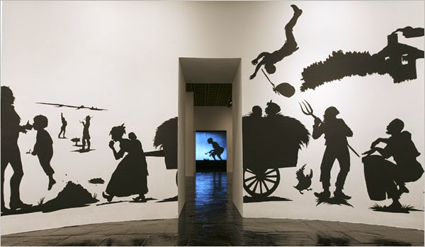 Black silhouette scenes depicting life in antebellum south on two walls, in the middle of photo is a doorway between the walls that depicts a silhouetted person against a blue sky background.