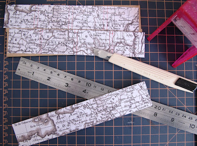 Pieces of scrapbooking paper showing a vintage map of France laid out on a cutting matt with a metal ruler, a knife and a sticker machine.