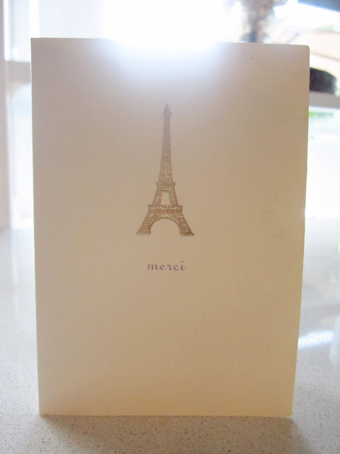 "Cream colored card with the  Eiffel Tower and ""Merci"" written below it"