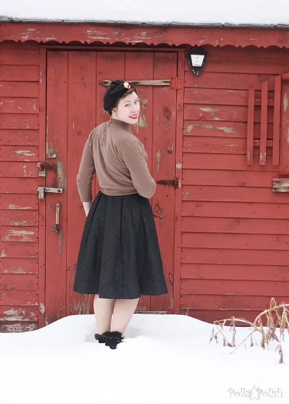 Wearing a black turban, brown sweater, and quilted skating skirt in front of a red shed