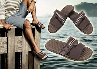 Os pés masculinos do ator Du Moscovis usando chinelos Cartago