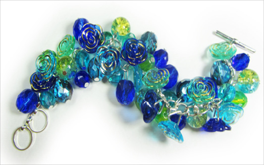 Dramatic bracelet has stunning blue flower buttons and clusters of shiny Czech beads