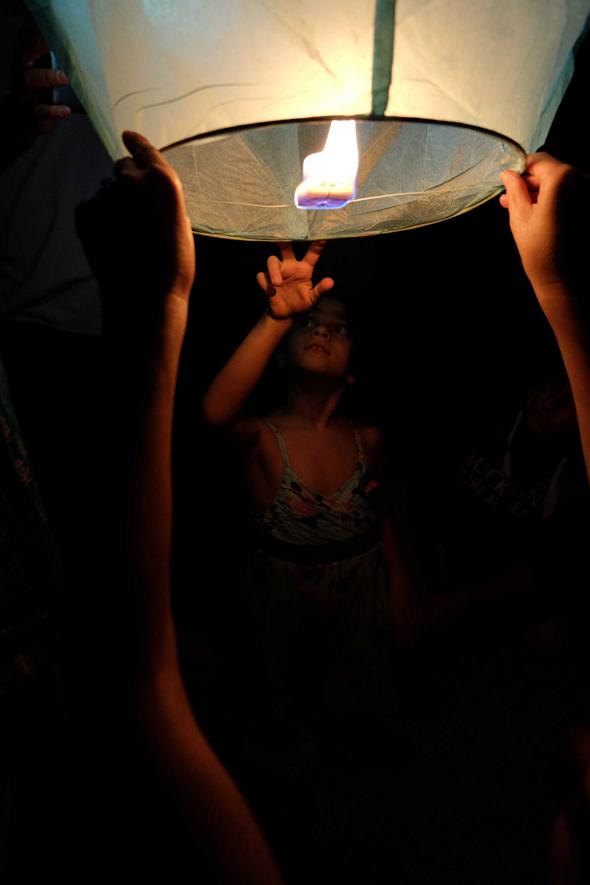 Fotografia di ragazza che accende una lanterna cinese volante