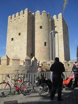 Vista de la Torre de la Calahorra y de una persona usuaria de silla de ruedas en sus inmediaciones.