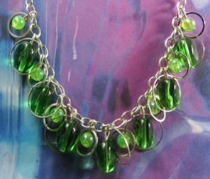 Necklace has green beads encircled with silver rings that hang from a single plunging chain