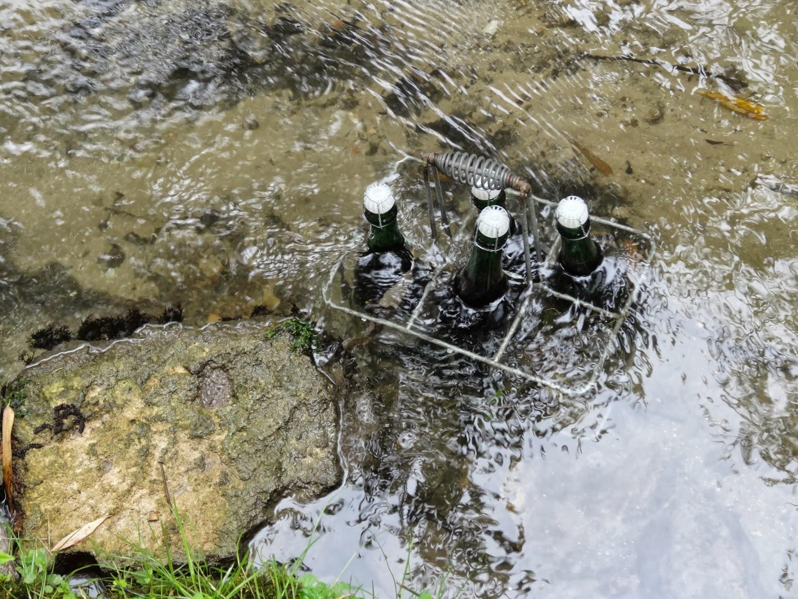 Des bouteilles de cidre attendent le visiteur, au frais dans la rivière...