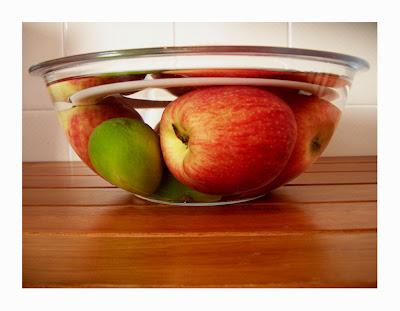 Na metade inferior da imagem, vê-se uma superfície de madeira marrom de tábuas estreitas horizontais. Sobre a superfície, centralizada na imagem, é vista a lateral de uma tigela de vidro transparente, redonda e com água. Vê-se uma tampa branca redonda submersa, mais abaixo três maças vermelhas e dois limões verdes, as frutas estão deformadas pelo efeito produzido pela água e o vidro transparente. Ao fundo vê-se parte de uma parede com azulejos beges.