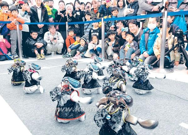 SEJUMLAH orang menyaksikan beberapa robot yang menari.