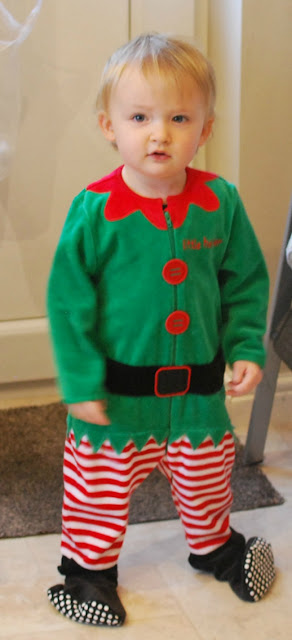 picture of toddler in Elf suit that's too big and feet are hanging off