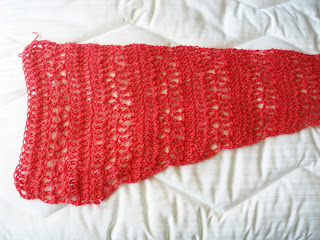 Coral colored lace shawl worked just past the center point