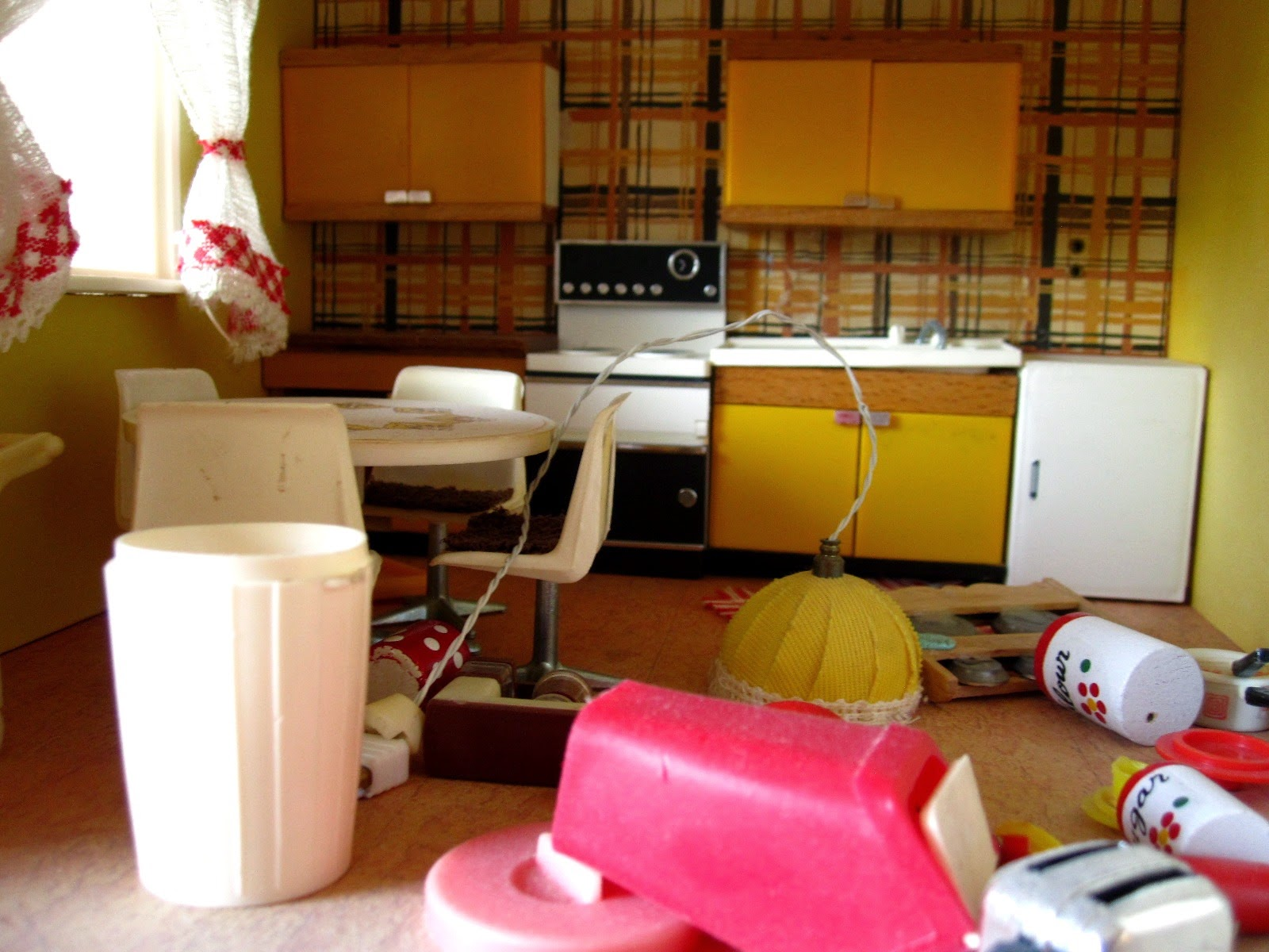 Messy vintage Lundby dolls house kitchen with dusty furniture and items strewn across the floor.