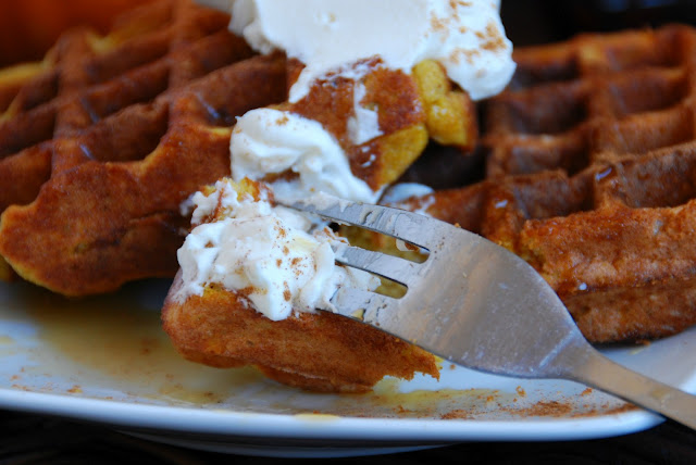 close up of pumpkin waffle and whipped cream bite on fork