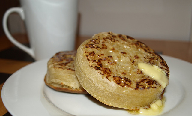 Two crumpets, dripping with butter, with a cup of tea in the background