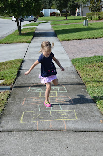 prekindergarten child hopping on a hopscotch board