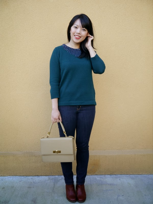 Forest green pullover sweater embellished with navy blue stones, dark wash skinny jeans, cognac leather ankle boots, taupe top-handle bag.