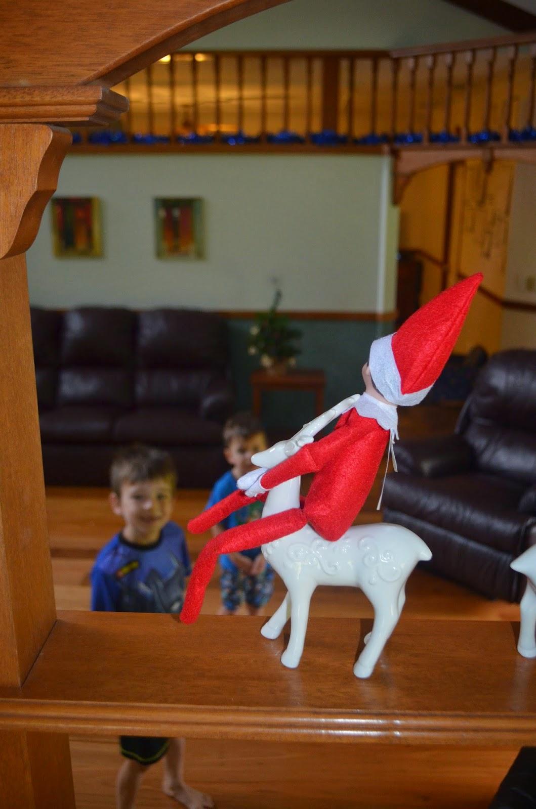Elf on the Shelf riding a reindeer