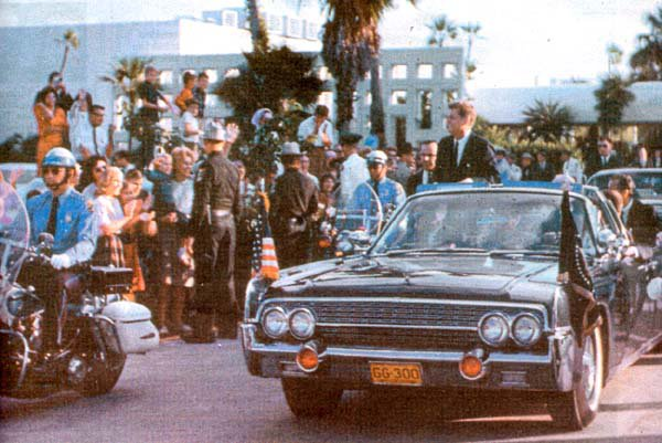 11/18/63: SA SAM SULLIMAN BESIDE JFK'S LIMO, POLICE LINING STREET FACING CROWD, ETC