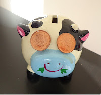 A piggy bank with two pennies as eyes