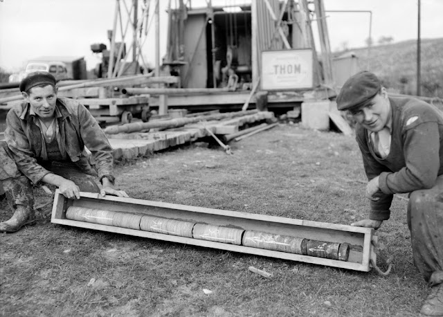 Archerbeck Borehole, Canonbie, Dumfriesshire. A length of core just removed from the core barrel, boxed and marked ready for transport to the core-shed.  A length of core just removed from the core barrel, boxed and marked ready for transport to the core-shed. Note how the core comes out in sections, this is typical. The 'way up' of the core is marked on each piece. The reamer can be seen to the right of the driller on the left.