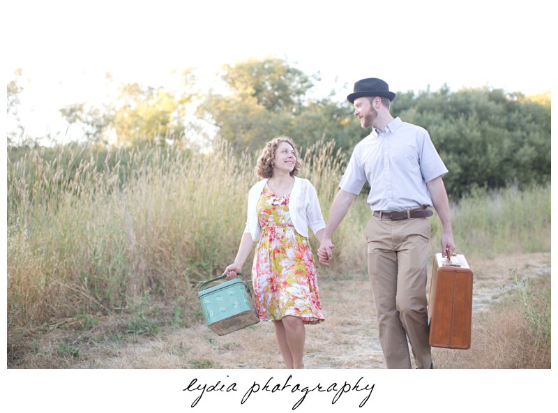 Bride and groom with luggage and picnic basket at lifestyle engagement portraits in the Bay Area of California