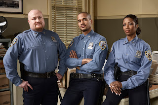 Three uniformed officers stand in the squad room.