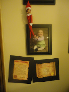 Diary of a crazed mommy timmy the elf is here day 1 timmy sat on top of emmas baby pictures that first morning with the adoption paper and a letter from santa stuck on the wall below him spiritdancerdesigns Images