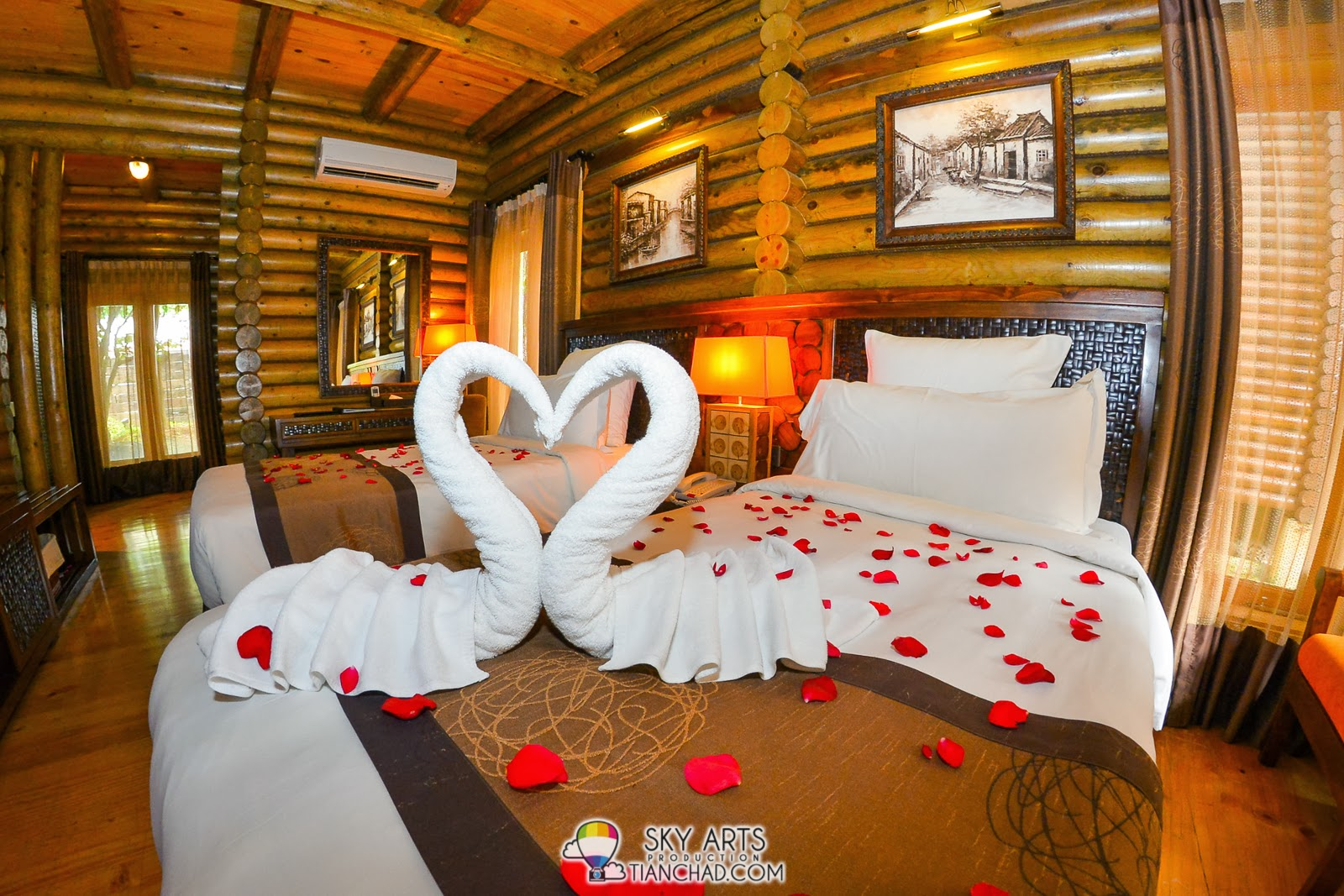 Room decorated with hand folded swan towels and rose petals on the bed
