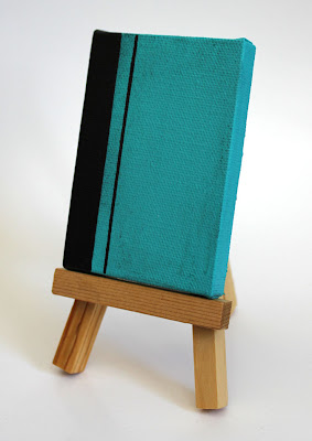turquoise and black color field painting on an easel