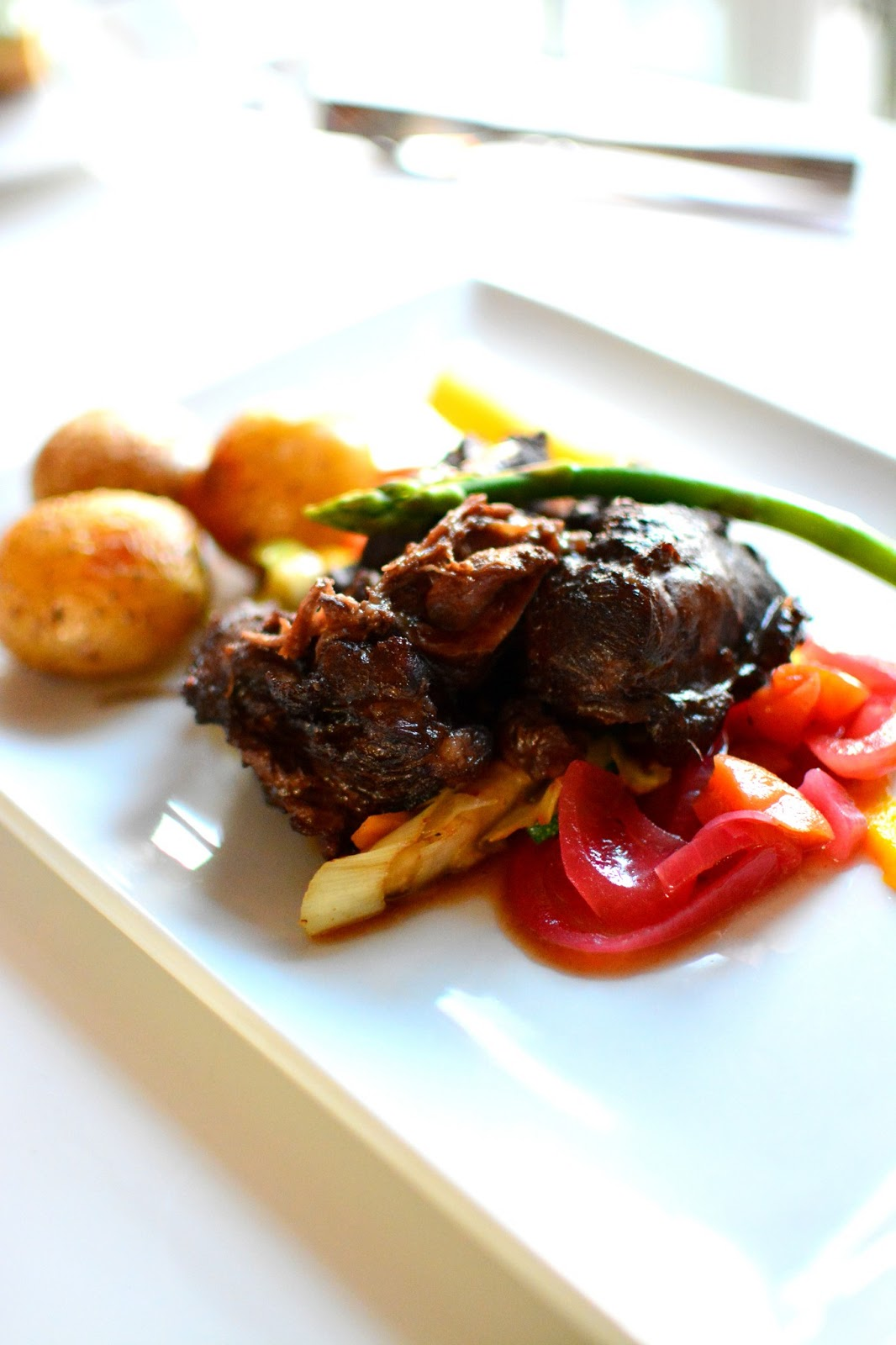 The braised pork cheeks with red onion and apricot saute, baked root ...