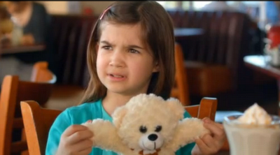 girl holding teddy bear's arms out and asking 'bear arms?'