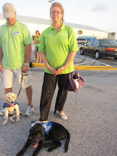 Tabina, a yellow lab, and Coach, a black goldadore, are  the babies of the group.  They are both four months old.  Here they are waiting patiently in the parking lot for the helicopter to taxi away. Photo by Carolyn Hersh.