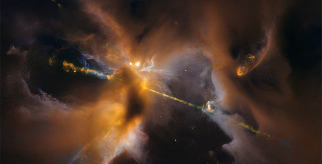 The two lightsabre-like streams crossing the image are jets of energised gas, ejected from the poles of a young star. If the jets collide with the surrounding gas and dust they can clear vast spaces, and create curved shock waves, seen as knotted clumps called Herbig-Haro objects.  Credit: ESA/Hubble & NASA, D. Padgett (GSFC), T. Megeath (University of Toledo), and B. Reipurth (University of Hawaii)