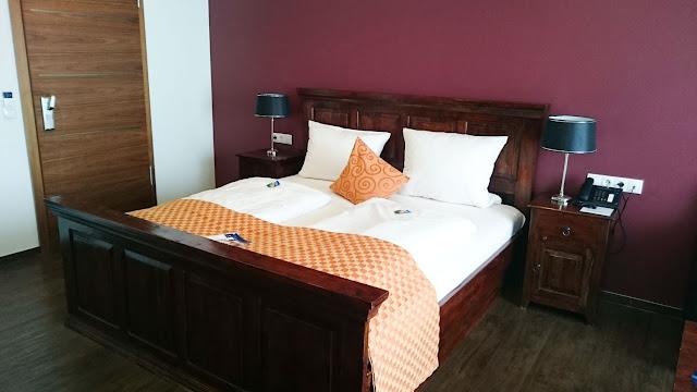 Bett aus Echtholz im Kapitänszimmer des River Side Hotels