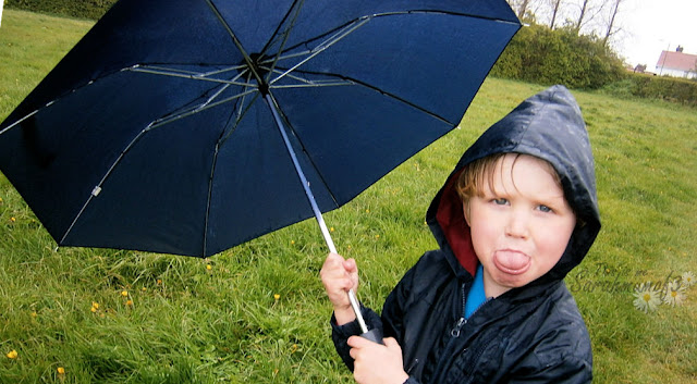 young boy in rain with umbrella
