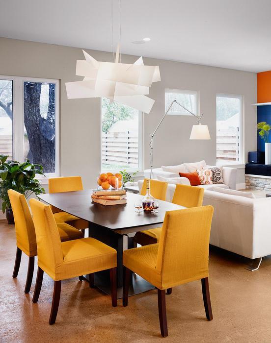 Decoração de sala de estar integrada com sala de jantar utilizando luminária de piso e pendente sobre a mesa.