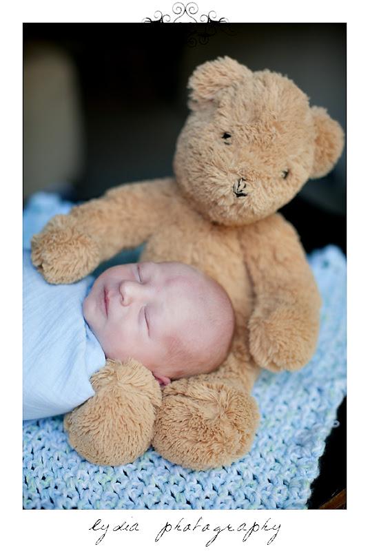 Baby boy sleeping on teddy bear at lifestyle newborn portraits at William Jessup University in Rocklin, California