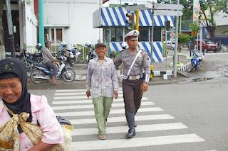 polisi-menyebrangkan-orang-di-jalan