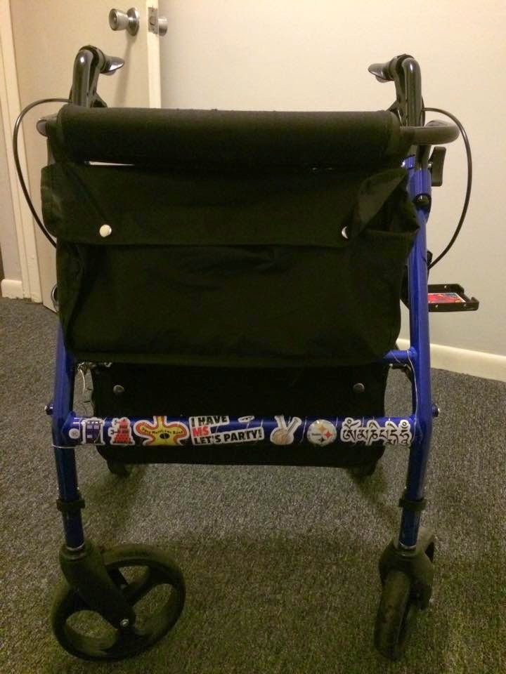 Photograph: The front of a rollator walker. Along the front are a series of indistinct stickers. On the side is an open cup holder.