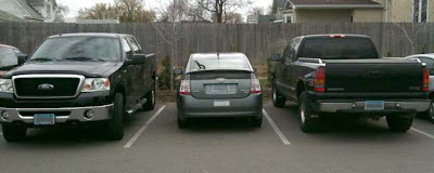 Gray Prius parked between two black full-sized pickup trucks