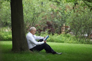 businessman reading under a tree
