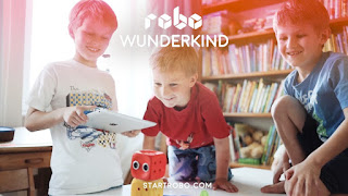 Children playing with iPad and robot