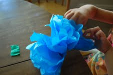 preschooler makes flowers from tissue paper for easy craft