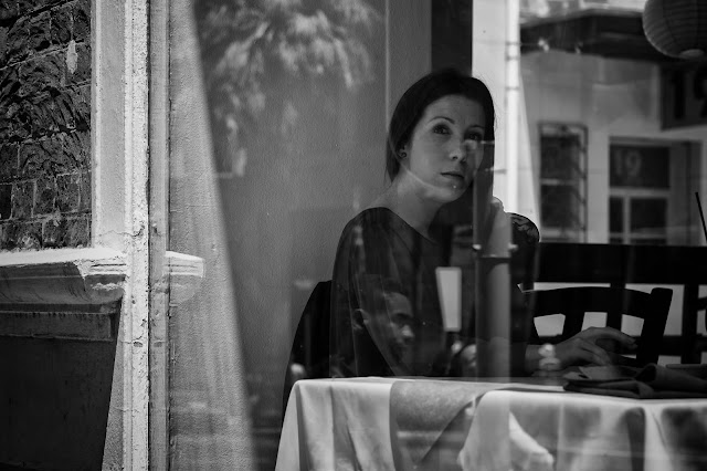 A woman in the window of a restaurant in this Cape Town street photo