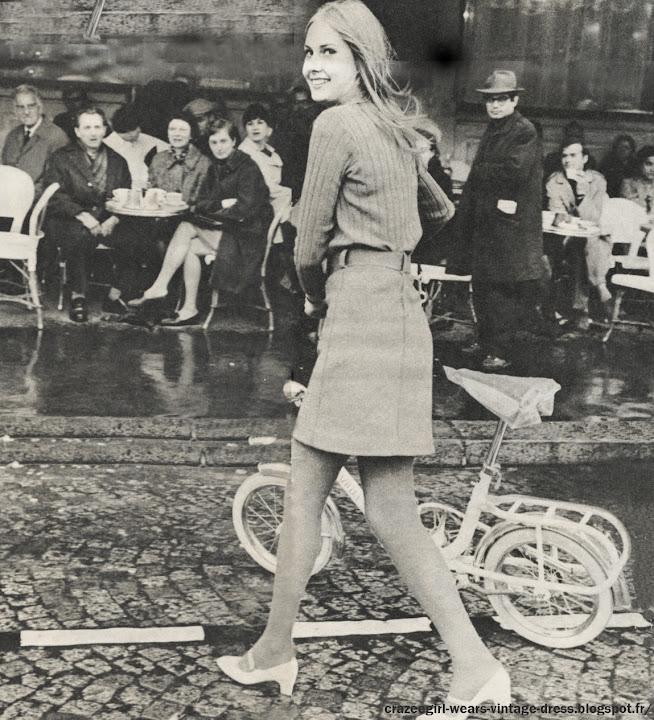 """Les Mini Jupes se risquent dans les rues de Paris - 1966 Dans le Paris des fêtes de Pâques , envahi par les Anglaises , les mini jupes testent le badaud .     « Lundi : pourquoi pas moi ? Après tout je n'ai que dix-sept ans et si je n'ose pas maintenant, je n'oserai jamais... J'ose ? Je n'ose pas ? J'ai feuilleté les magazines, Françoise Hardy a bien osé elle. Je suis quand même un peu plus grosse que Françoise, et maman ne voudra jamais. Jeudi ; j'ai osé. Après tout le short ce n'est pas tellement différent, un copain m'a demandé « Tu as fait une économie de tissu ? » J'ai souri. « Non, ai-je répondu, je vais faire du tennis. » Il y a eu un ou deux coups d'œil désapprobateurs. J'ai tiré sur ma jupe comme si je voulais qu elle s'allonge. Et puis j'ai regardé les autres : sont-elles mieux que moi ? Après tout j'ai seulement un peu froid aux jambes. Samedi je suis allée danser au « Cherry Lane ». Là je n'ai pas eu le moindre complexe, je n'étais plus la seule. Tout de même je suis fière. J'ai vraiment l'impression d'avoir été le pionnier de quelquç chose ! »   Ceci est l'extrait d'un journal intime d'une « mini-jupe-girl ». Nous vous le livrons tel qu'il fut écrit sans aucun commentaire. Suzy , une cover girl londonnienne passe devant les """" Deux Magots """" sur une bicyclette dont les roues ont rétréci comme sa jupe . Les Parisiens n'avaient pas été aussi étonnés depuis le New-Look . Entre Paris et Londres, le match est ouvert . Pour l'instant l' Angleterre gagne  de quelques centimètres . Mais en France , l' exemple des mini jupes est venu d'en haut : tout à commencé cet hiver avec les quelques cinq cents modèles des grands couturiers dont le plus court était au genou Une nuit au Cherry Lane à Saint Germain Des Près , les mini jupes sont à l'honneur . A la question """"Les porteriez vous à midi ? """" , la moitié des danseuses a répondu """"seulement le soir !"""" .Une élégante s'aventure rue Lepic. Sur elle, la robe ultra-moderne d'un grand couturier. Les marchandes la prennent à """