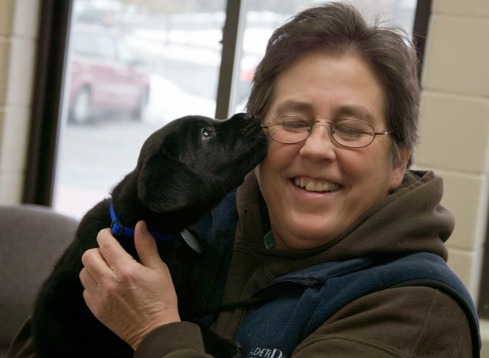 A woman with short brown hair and glasses, wearing a brown hooded sweatshirt and blue vest, is holding a small black lab puppy in her hands. The puppy is licking her right cheek and she is squinting and smiling.